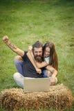 Couples dans l'ordinateur portable d'utilisation d'amour sur la nature, surfing sur Internet Photos stock