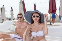 Couples dans l'usage de plage d'été dans une station de vacances Photo libre de droits