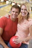Couples dans la bille et le sourire de fixation de ruelle de bowling Images libres de droits