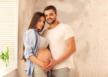 Couples dans la caresse enceinte d'amour, bébé de attente Photographie stock