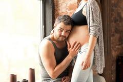 Couples dans la caresse enceinte d'amour, bébé de attente Jour du `s de mère Photographie stock libre de droits