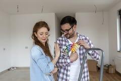 Couples dans la chambre vide choisissant des couleurs pour la peinture photo stock