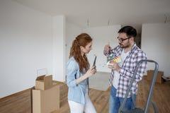 Couples dans la chambre vide choisissant des couleurs pour la peinture photos stock