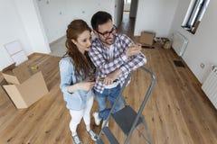 Couples dans la chambre vide choisissant des couleurs pour la peinture photo libre de droits