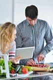 Couples dans la cuisine à la maison utilisant la Tablette électronique Photographie stock