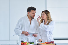 Couples dans la cuisine à la maison utilisant la Tablette électronique Photos libres de droits