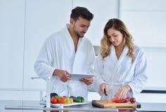 Couples dans la cuisine à la maison utilisant la Tablette électronique Image stock