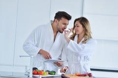Couples dans la cuisine à la maison utilisant la Tablette électronique Photo stock