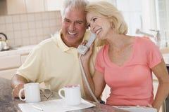 Couples dans la cuisine avec du café utilisant le téléphone Photographie stock