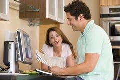 Couples dans la cuisine avec l'ordinateur et le journal Images stock