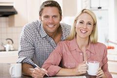 Couples dans la cuisine avec le journal avec du café Photo stock