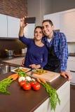 Couples dans la cuisine faisant cuire et prenant le selfie avec Photos libres de droits