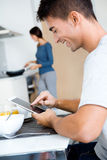 Couples dans la cuisine préparant le petit déjeuner et l'Internet de lecture rapide Photos stock