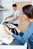 Couples dans la cuisine préparant le petit déjeuner et l'Internet de lecture rapide Photographie stock libre de droits