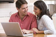 Couples dans la cuisine utilisant l'ordinateur portatif et le sourire Photographie stock