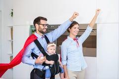 Couples dans la fille de transport de costume de super héros Photo stock