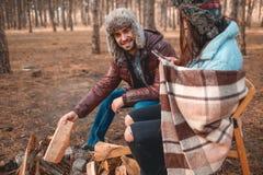 Couples dans la forêt d'automne près du feu Images stock