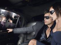 Couples dans la limousine avec des paparazzi par la fenêtre Images stock
