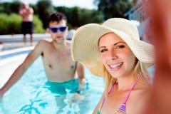 Couples dans la piscine prenant le selfie Été et eau Photographie stock libre de droits