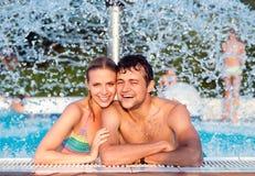 Couples dans la piscine swimmning sous éclabousser la fontaine La chaleur d'été Photographie stock libre de droits