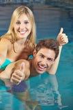 Couples dans la piscine tenant des pouces  Photographie stock