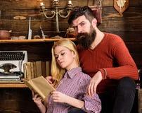 Couples dans la poésie de lecture d'amour en atmosphère chaude Madame et homme avec la barbe sur les visages rêveurs avec le livr Photos stock