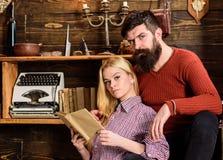 Couples dans la poésie de lecture d'amour en atmosphère chaude Madame et homme avec la barbe sur les visages rêveurs avec le livr Image libre de droits