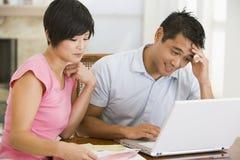 Couples dans la salle à manger avec l'ordinateur portatif semblant malheureux Photographie stock libre de droits