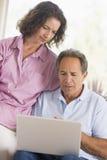 Couples dans la salle de séjour avec l'ordinateur portatif Photo libre de droits