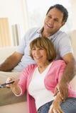 Couples dans la salle de séjour avec le sourire à télécommande Image libre de droits