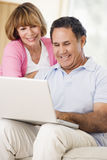 Couples dans la salle de séjour avec le sourire d'ordinateur portatif Image stock