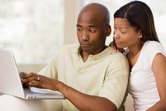 Couples dans la salle de séjour utilisant l'ordinateur portatif Photo libre de droits