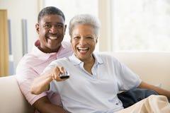 Couples dans la salle de séjour utilisant le sourire à télécommande Photographie stock