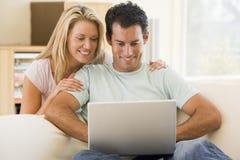 Couples dans la salle de séjour utilisant le sourire d'ordinateur portatif images libres de droits