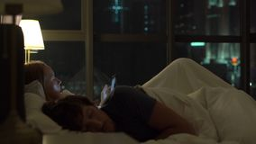Couples dans le bâti femme à l'aide d'un PC de comprimé tandis que l'homme essaye de dormir des problèmes dans le mariage et les  banque de vidéos