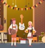 Couples dans le bar portant la bière traditionnelle de boissons de vêtements en partie d'Oktoberfest de barre Photo stock