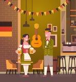 Couples dans le bar portant la bière traditionnelle de boissons de vêtements en partie d'Oktoberfest de barre Photos stock
