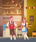 Couples dans le bar portant la bière traditionnelle de boissons de vêtements en partie d'Oktoberfest de barre Photos libres de droits
