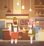 Couples dans le bar portant la bière traditionnelle de boissons de vêtements en partie d'Oktoberfest de barre Image libre de droits