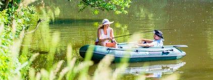 Couples dans le bateau sur la pêche d'étang ou de lac Images stock