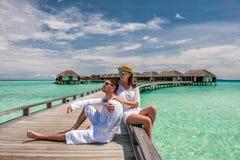 Couples dans le blanc sur une jetée de plage chez les Maldives images libres de droits