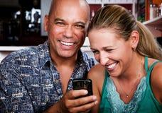 Couples dans le café avec le téléphone portable Image stock