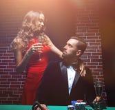 Couples dans le casino jouant le tisonnier sur le feutre de vert Photo stock