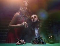 Couples dans le casino jouant le tisonnier sur le feutre de vert Photographie stock libre de droits