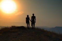 Couples dans le coucher du soleil Photographie stock libre de droits