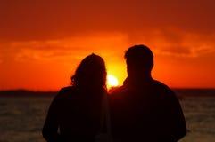 Couples dans le coucher du soleil de observation d'amour Photo stock