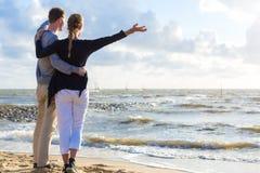 Couples dans le coucher du soleil romantique sur la plage Photographie stock