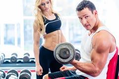 Couples dans le gymnase de forme physique avec des haltères soulevant le poids Photos libres de droits