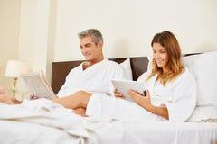 Couples dans le journal et la tablette de lecture de chambre d'hôtel Photos stock