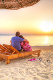 Couples dans le lever de soleil de observation d'étreinte ensemble Photographie stock libre de droits